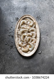 Fresh raw  shrimps without head on ice in a metal oval dish. Top view