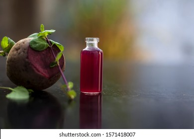 Fresh raw sliced beetroot along with some mint leaves and its extracted essence oil in a tiny glass bottle.Horizontal shot with blurred background.