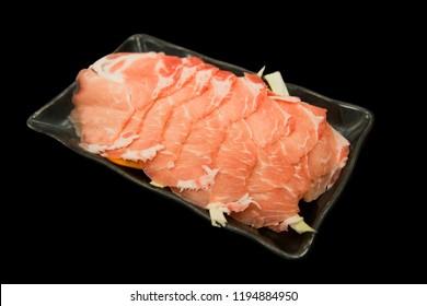 Fresh raw sliced pork on black background