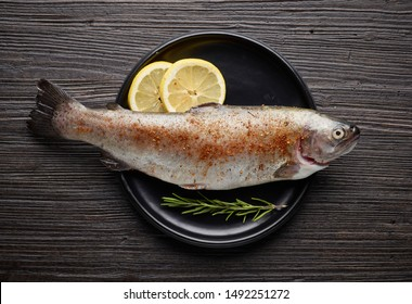 fresh raw spicy trout fish on wooden kitchen table, top view