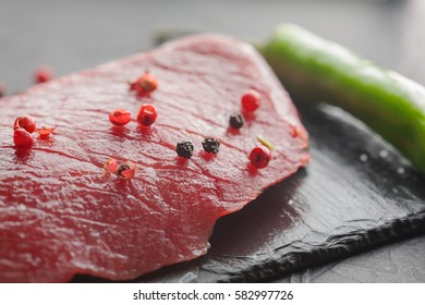 fresh raw steak with chili on the black stone