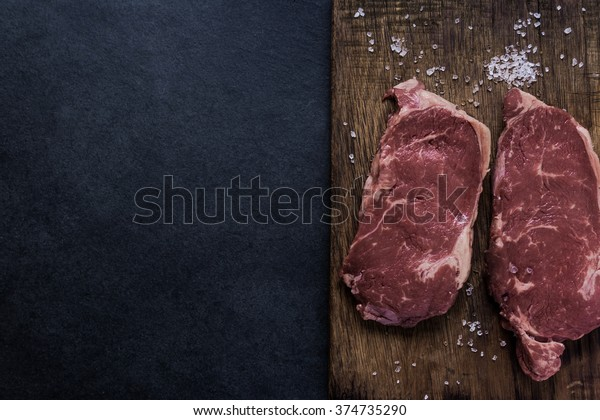 Fresh raw stirlion beef steaks with salt, from above on wooden board, dark slate background.