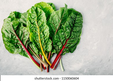 Fresh raw swiss rainbow chard leaves on gray stone background. Top view