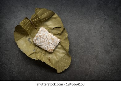 Fresh raw tempeh wrapped in leaf on dark background. Top view.