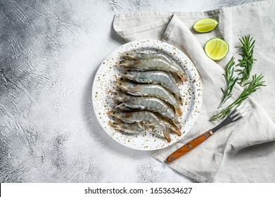 Fresh raw tiger prawns, shrimps and spices on a white plate. Gray background. Top view. Copy space