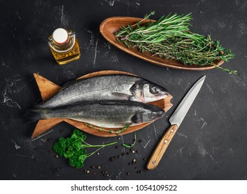 Fresh raw trout fish trout, knife for cutting. Ingredients for raw trout fish are pepper, herb thyme, rosemary, parsley, olive oil. Dark background. Top view.