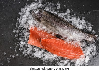 Fresh raw trout fish steak and whole fish with spices on ice over dark stone background. Creative layout made of fish, top view, flat lay
