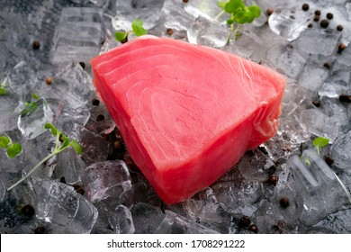 Fresh raw tuna fillet on ice cut into steak on a stone background with seasonings and herbs
