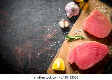 Fresh raw tuna on a cutting Board with lemon and garlic. On dark rustic background