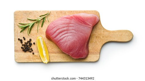 Fresh raw tuna steak on cutting board.
