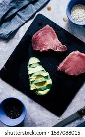 Fresh raw tuna steak ready to be prepared  for cooking on a stone lavic plate  with pink salad and avocado slice on a plate top view over a wooden cutboard background - Shutterstock ID 1587088015
