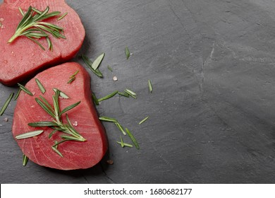 Fresh raw tuna steak with rosemary on black stone background, top view