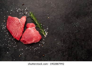 Fresh raw tuna steaks with rosemary and spices on a stone background with copy space for your text