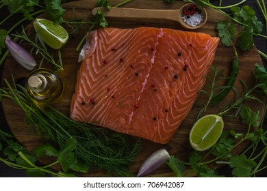 Fresh, raw uncooked salmon fillet with lemons, herbs and spices on a wooden background, top view.