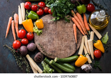 Fresh raw vegetable ingredients for healthy cooking or salad making with rustic wood board in center, top view, copy space. Diet or vegetarian food concept, horizontal composition