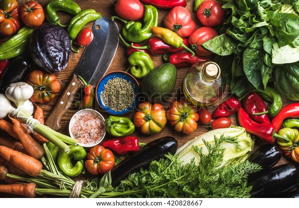 Fresh raw vegetable ingredients for healthy cooking or salad making, top view. Olive oil in bottle, spices and knife. Diet or vegetarian food concept