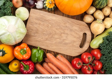 Fresh raw vegetables and cutting board, top view