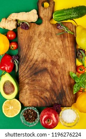 Fresh raw vegetables, fruit and  ingredients for healthy cooking salad making around vintage wooden cutting board on color background, top view, place for text. Diet  vegan food, vegetarian. Flat lay