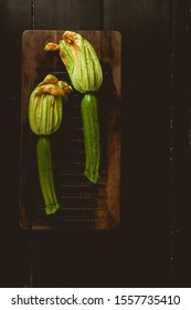 Fresh raw zucchini (courgette) with flowers and Squash blossoms , on a wooden board , top view, natural light.