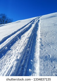 Fresh razer tracks in powder snow under clear blue sky at winter