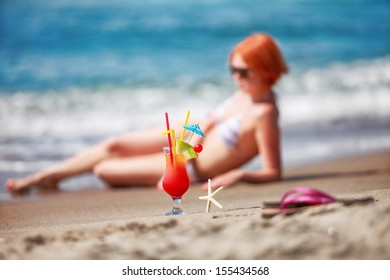 fresh red alcohol free cocktail on a sand with blurred redhaired girl taking a sunbath in background
