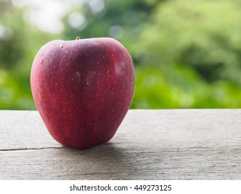 Fresh red apple on wooden table in garden with copy space