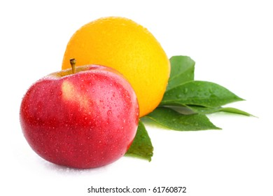 Fresh red apple and orange (with water drops and leaves) on white