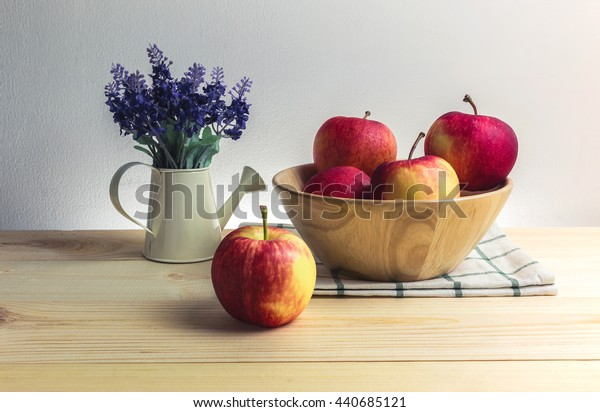 Fresh red apple still life concept. There are apple on the floor and in the wood bowl. Vintage tone