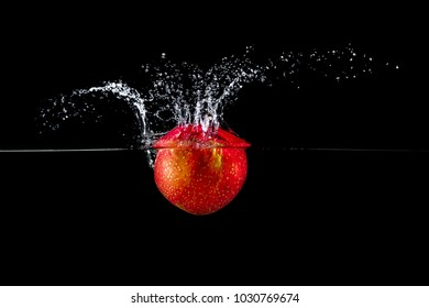 fresh red apple in water splash on black background