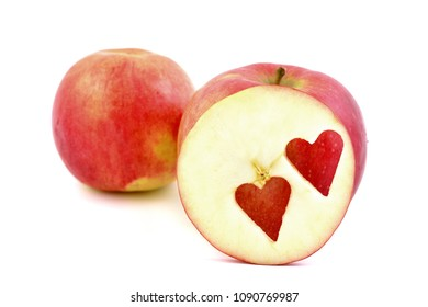 Fresh red apples with a heart shaped cut-out on white background.