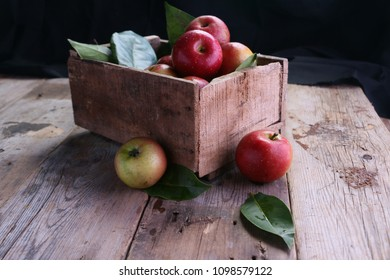 Fresh red apples in wooden box with dark background.