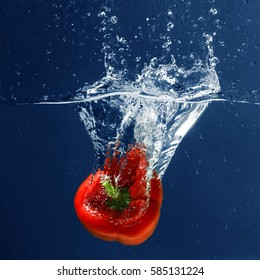 Fresh red bell pepper falling in water on blue background