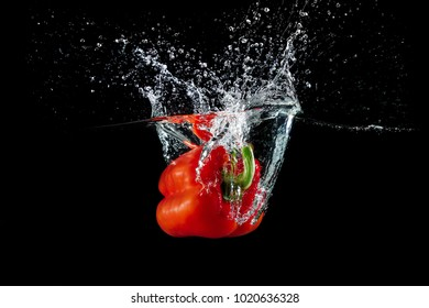 fresh red bell pepper in water with splash on black background