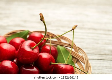 Fresh red cherries in basket on wooden background close up