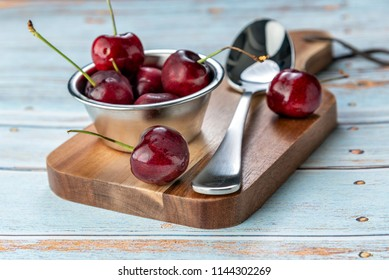 Fresh red cherries and Ice cream with a silver spoon on a small wooden chopping board
