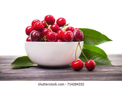 fresh red cherry fruit in plate on wood table isolated on white background