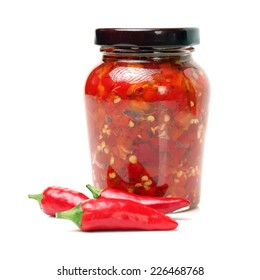 Fresh red chilly and bottled chili sauce over white background