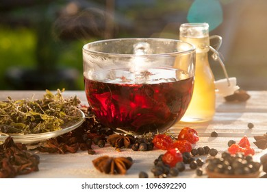 Fresh red chrysanthemum tea with rose petals of hibiscus in a transparent glass mug on a white wooden table with red berries and thyme
