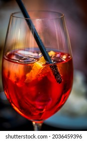 Fresh red cocktail with ice cubes and a straw, close-up photo of light alcoholic drink