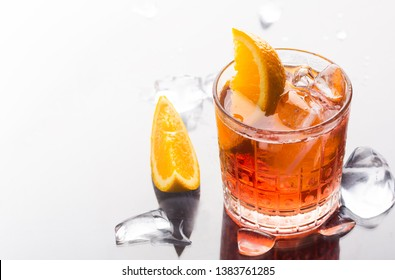 Fresh red colorful alcoholic cocktail Aperol Spritz with orange and ice in glass on white background with reflections and copy space