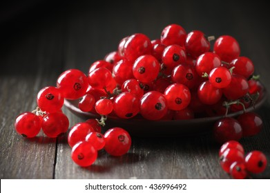 Fresh red currants in plate on dark rustic wooden table. Shallow DOF.