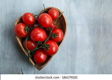 fresh red delicious tomatoes  in the heart shape plate on an wooden tabletop with place for text