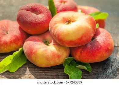 Fresh red flat peaches with leaves on a dark wooden background, sunny summer day, selective focus