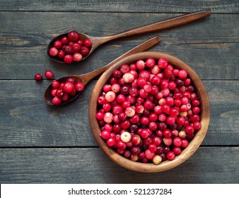 Fresh red forest cranberry in a round bowl with a wooden spoons on a wooden table surface. Autumn harvest of wild berries
