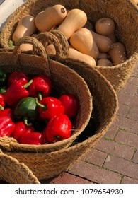 Fresh red heel peppers and squash ready for sale in baskets along a small street in Europe.