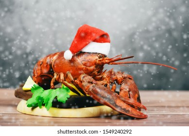 Fresh red lobster with christmas hat shellfish cooked in the seafood restaurant / Steamed lobster dinner food on wooden christmas table setting with snow celebrate in holiday winter festive