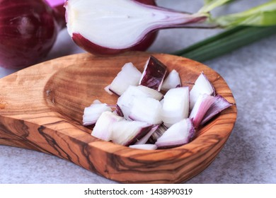 Fresh red onion feathers and cut into pieces. Fresh Red onion on grey background.