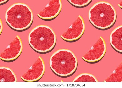 Fresh red orange or grapefruit on a peach color background. Beautiful cut juicy slices. Pattern seamless tropical fruit photo.