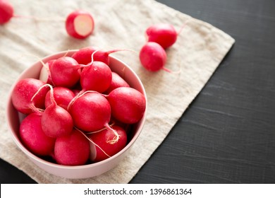 Fresh red radishes in a pink bowl over black surface, low angle view. Copy space.