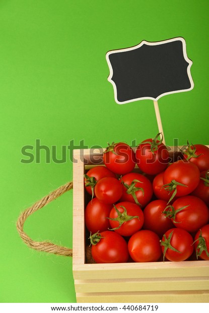 Fresh red ripe cherry tomatoes in small wooden box with black chalkboard price sign tag over green background, high angle view